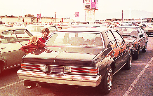 Vintage image of a children standing beside a car in a parking lot.