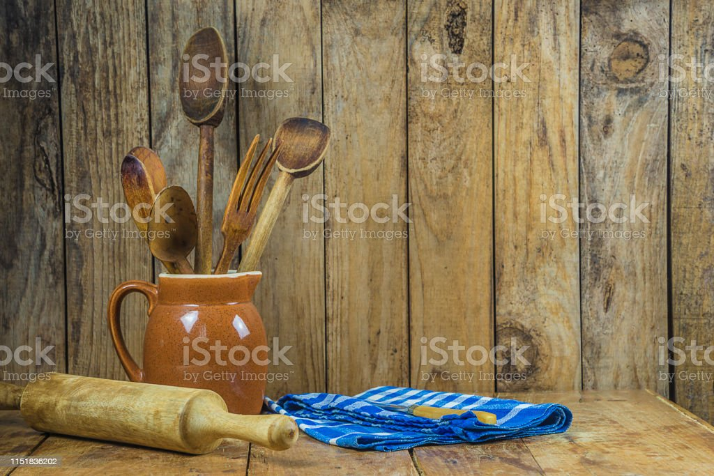 old kitchen utensils in jug, pastry roll, knife on checkered napkin...