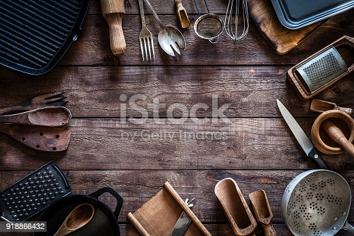 Top view of a rustic wooden table with vintage kitchen utensils placed all around the border making a frame and leaving useful copy space for text and/or logo at the center. Kitchen utensils included in the composition are cast iron pan, iron grill, spoons, kitchen knife, serving scoops, colander, cutting board, baking sheet, mortar and pestle, grater, sieve, forks and others. Predominant color is brown. Low key DSRL studio photo taken with Canon EOS 5D Mk II and Canon EF 100mm f/2.8L Macro IS USM