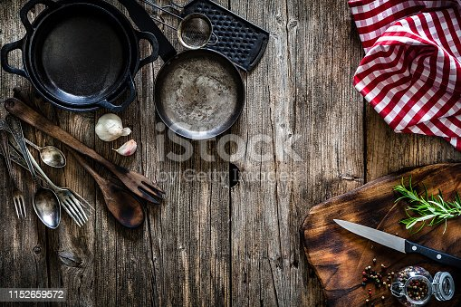 Cooking backgrounds: Top view of various vintage kitchen utensils placed at the top left of a rustic wooden table. At the opposite corner is a cutting board with a kitchen knife, a rosemary twig and a glass container with peppercorns. A crumpled red and white gingham tablecloth is at the top right. Useful copy space for text and/or logo. Kitchen utensils included in the composition are cast iron pans, grater, a small sieve, spoons, forks and others. Predominant color is brown. Low key DSRL indoors photo taken with Canon EOS 5D Mk II and Canon EF 24-105mm f/4L IS USM Wide Angle Zoom Lens