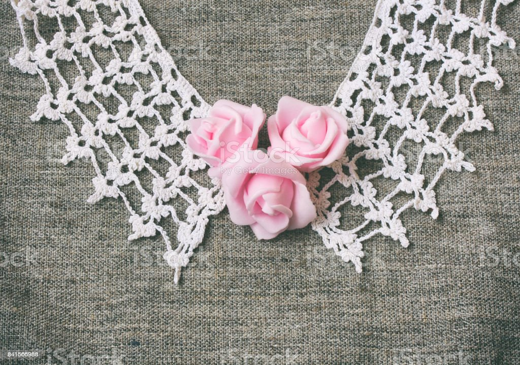 vintage knitted collar, pink roses on canvas fabric stock photo