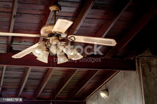 Vintage lamp with rotating ceiling Fan in wooden house.