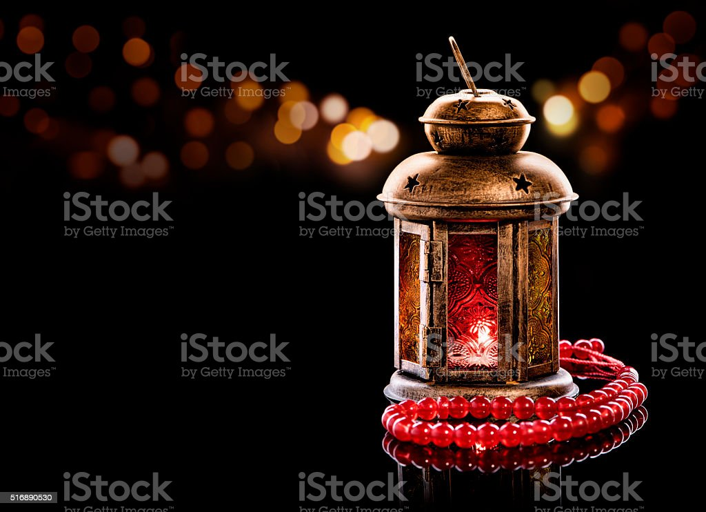 Vintage lantern with red rosary stock photo