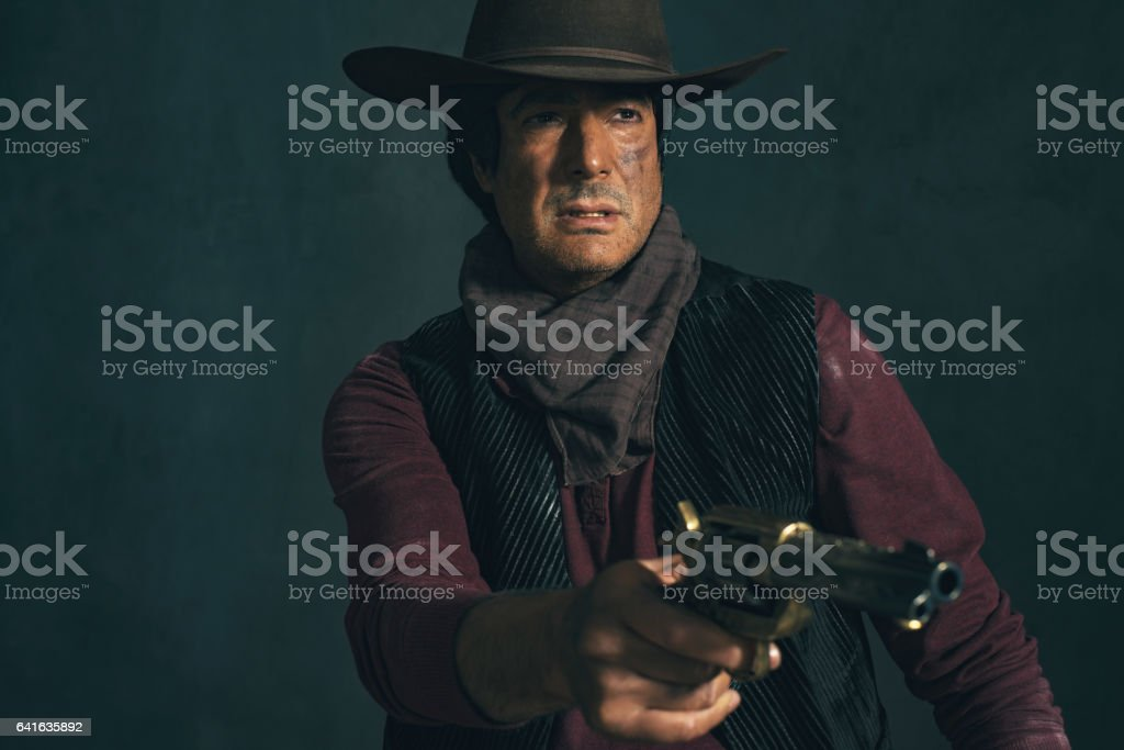 Vintage late 1960s spaghetti western actor. Shooting with revolver. stock photo