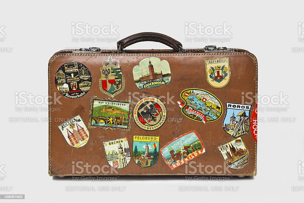 Vintage leather suitcase  with labels standing on the floor. stock photo