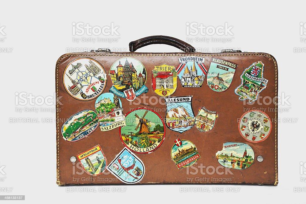 Vintage mala de viagem de couro com rótulos em pé no chão. - foto de acervo