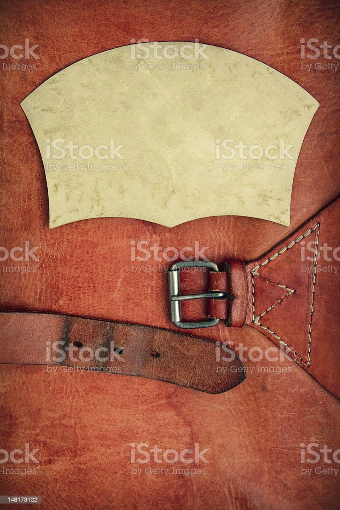 Vintage leather textured background with a buckle and paper frame royalty-free stock photo