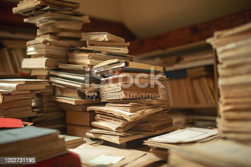 Library with archive of very old books and documents stored and unsorted. Big mess that looks beautiful.