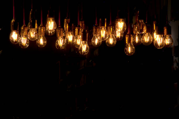Vintage light bulbs in a row, black background. stock photo