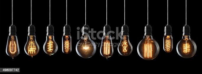 Set of vintage glowing light bulbs on black background
