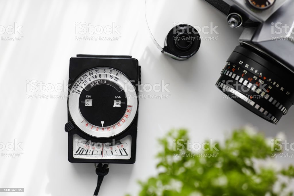Vintage Light Meter And Analog Film Camera On White Table