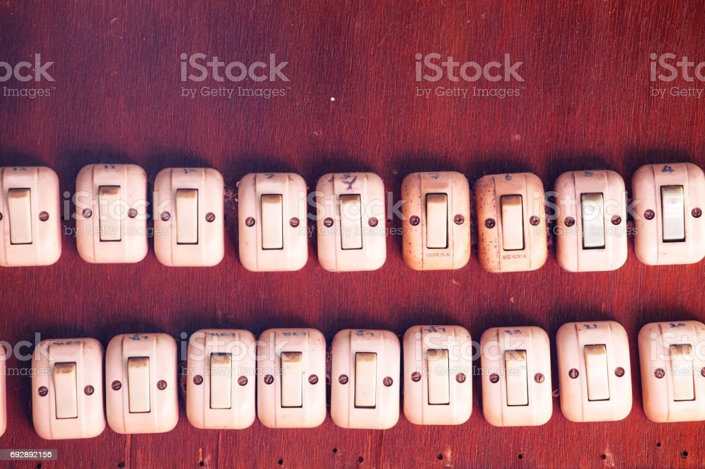 vintage light switch on wooden wall as background with copyspace. stock photo
