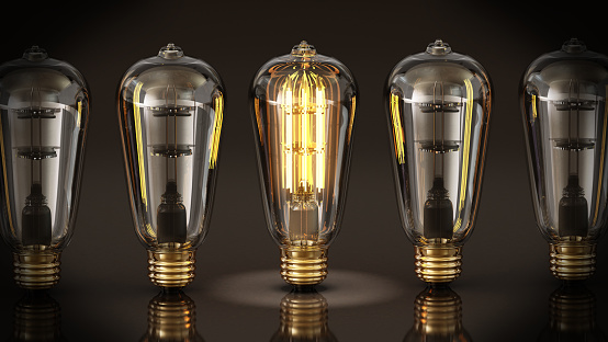 Vintage lit lightbulb standing at the middle of unlit lightbulbs. Creativity and uniqueness concept.
