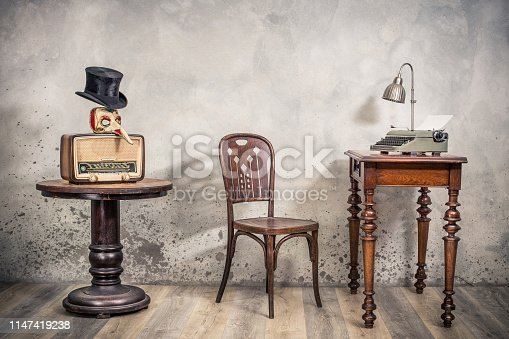 1065736660 istock photo Vintage loft room with antique chair, broadcast radio, carnival mask, cylinder hat, old typewriter and lamp on oak wooden desk front concrete wall background with shadows. Retro style filtered photo 1147419238
