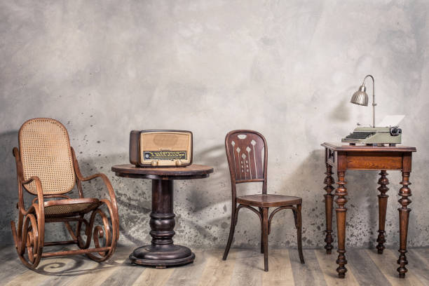 Vintage Loft Zimmer mit antikem Schaukelstuhl, Rundfunk-Radio, alter Schreibmaschine und Lampe auf Eichenholzschacht-Betonwand mit Schatten. Retro-Stil gefiltert Foto – Foto
