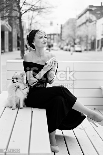 Vintage looking woman sitting on a city bench with her dog and a pastry box. She is dress to look like Audrey Hepburn, and the dog is a papillon spaniel. Vertical black and white full length outdoors shot with copy space. This was taken in Montreal, Canada.