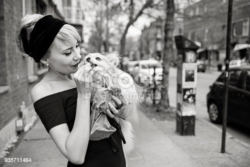 Vintage looking woman feeding her dog a piece of bagel. She is dress to look like Audrey Hepburn, and the dog is a papillon spaniel. Horyzontal black and white waist up outdoors shot with copy space. This was taken in Montreal, Canada.