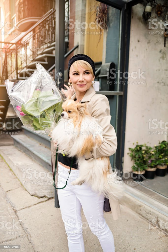 Vintage looking woman leaving a local store with dog in city. stock photo