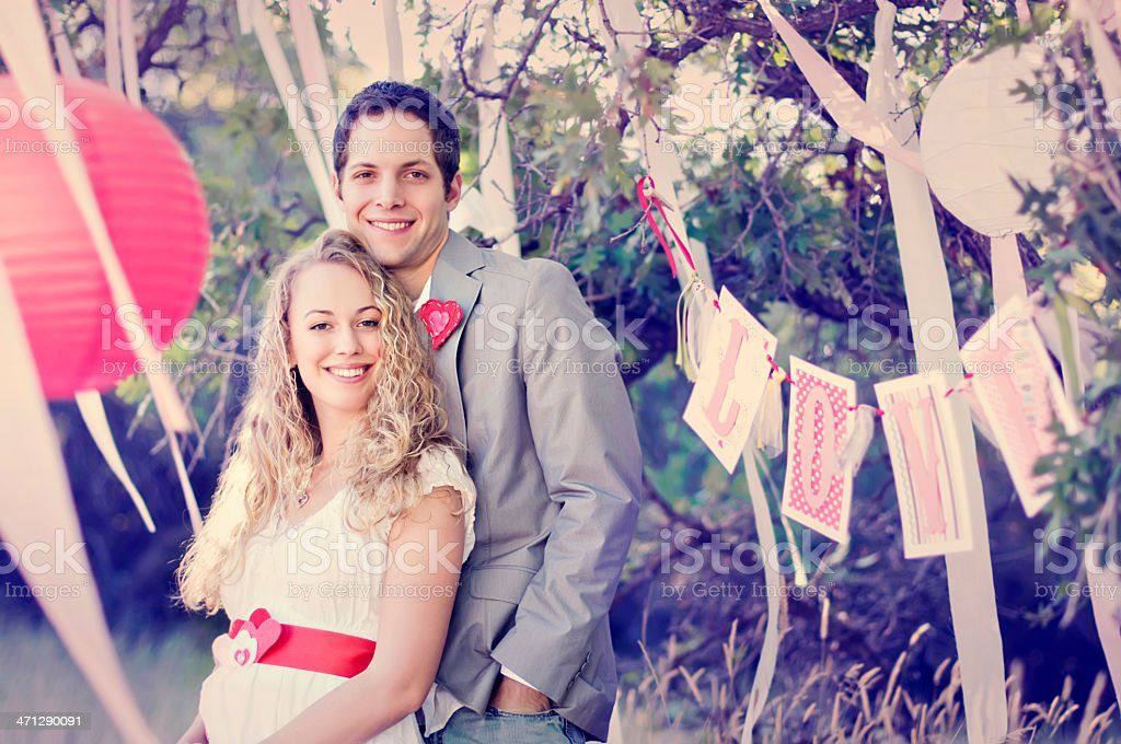 Vintage couple in love, standing in the trees with paper streamers...