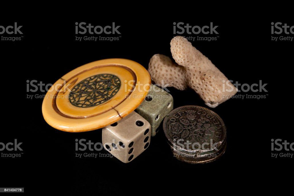 Vintage lucky charms. Antique poker chip, dice, squashed sixpences and coral. stock photo