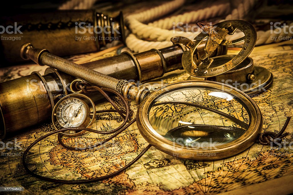 Vintage magnifying glass lies on an ancient world map royalty-free stock photo