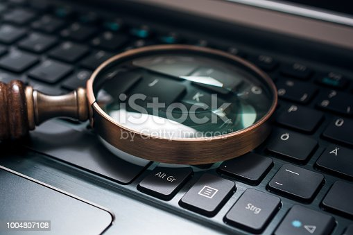 istock Vintage Magnifying Glass On A Black Notebook Keyboard - SEO Concept 1004807108