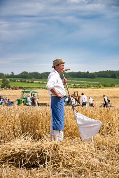 vintage man with scythe on the field stock photo