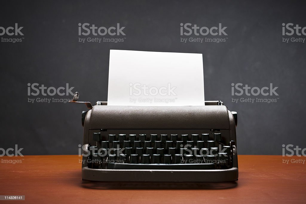 Vintage manual typewriter holds blank sheet of paper royalty-free stock photo