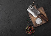 Vintage meat knife hatchet on vintage chopping board and black stone table background. Butcher utensils. Space for text