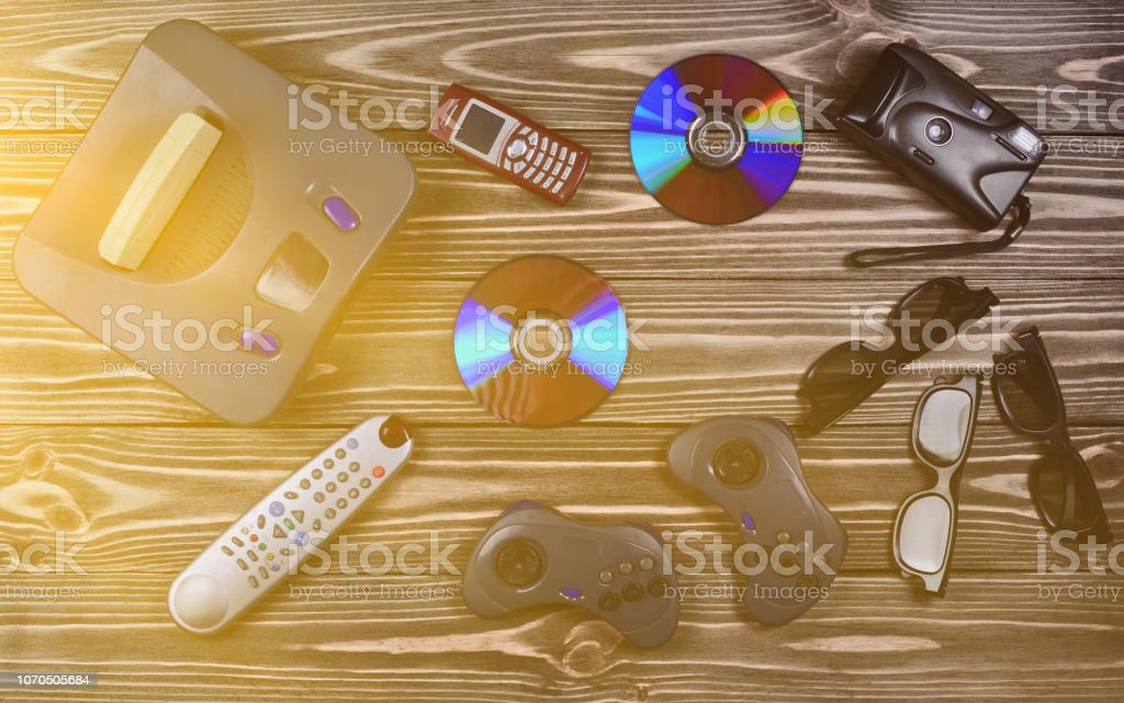 Vintage media and information technology. Entertainment 90s. Game console, gamepads, disks , phone, film camera on a wooden table. Top view. Flat lay. – zdjęcie