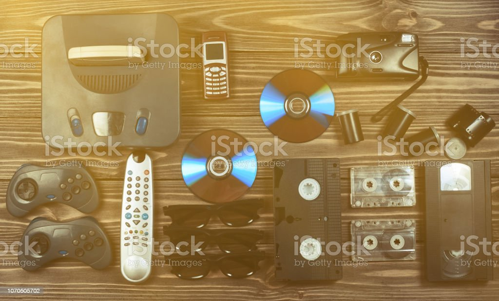 Vintage media and information technology. Entertainment 90s. Game console, gamepads, disks, audio cassettes, video cassettes, phone, film camera on a wooden table. Top view. Flat lay. – zdjęcie