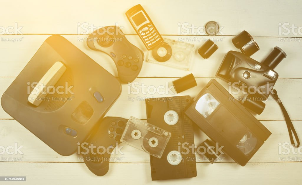 Vintage media and information technology. Entertainment 90s. Game console, gamepads, disks, audio cassettes, video cassettes, phone, film camera on a white wooden table. Top view. Flat lay. – zdjęcie