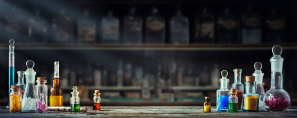 Vintage medications in small bottles on wood desk. Old medical, chemistry and pharmacy history concept background. Retro style. stock photo