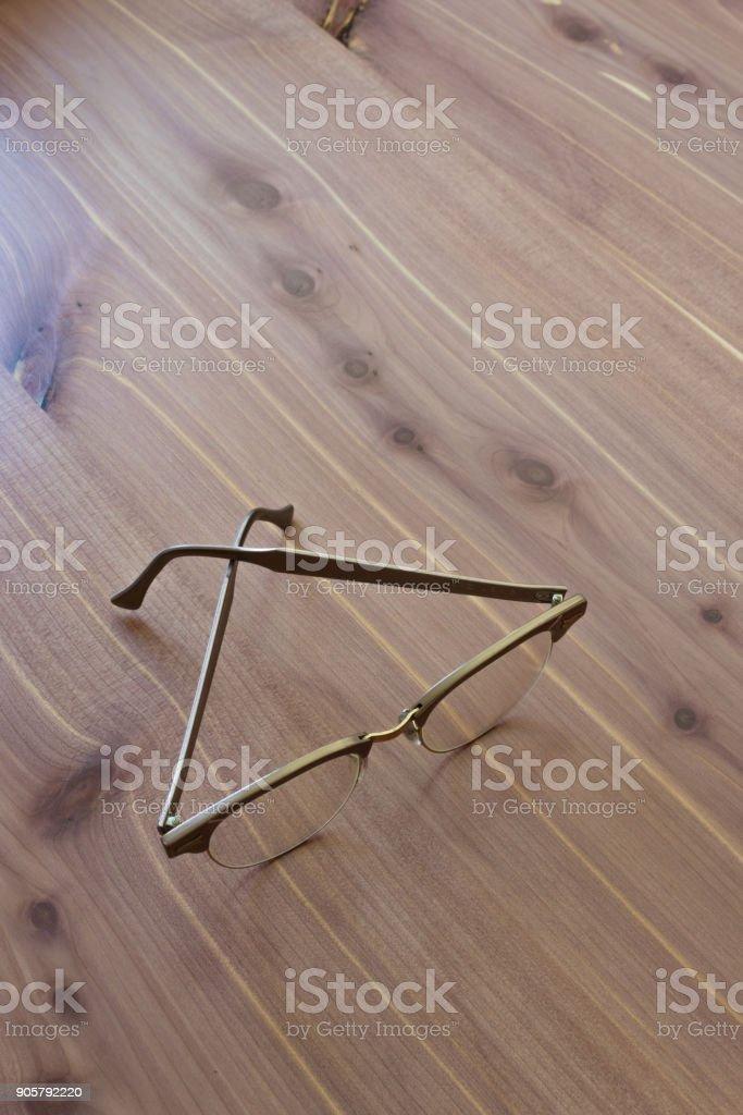 Vintage men horn rimmed style eyeglasses on neutral wood background, copy space stock photo
