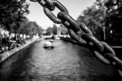 The section of large rusty metal chain running across the corner of image, with Amsterdam Canal and Tourist Boat on the background. Black and White Image with Selective Focusing.