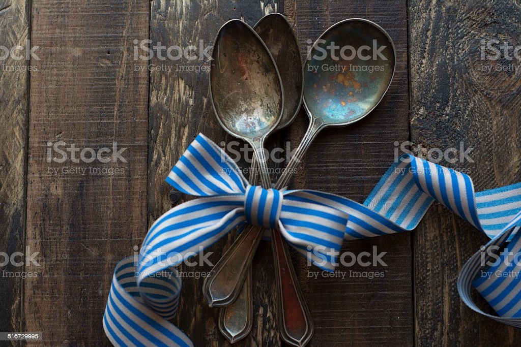 vintage metal spoons, ribbon and wooden background stock photo