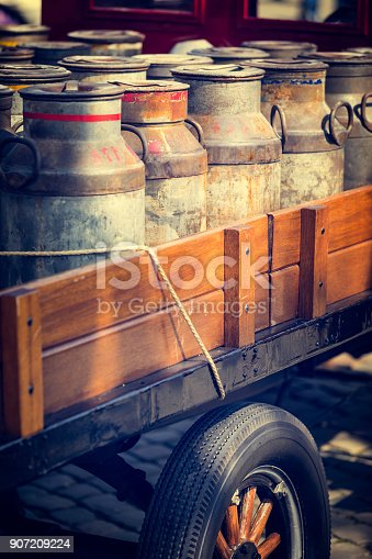 old car loaded with rusty milk cans