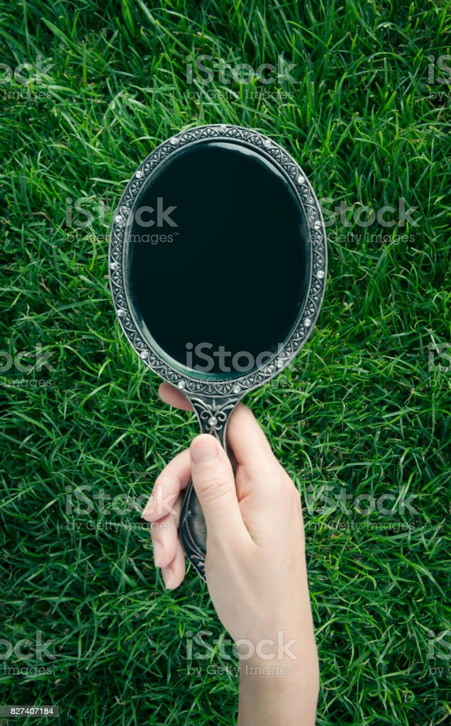Vintage Mirrorin hand over green lawn stock photo