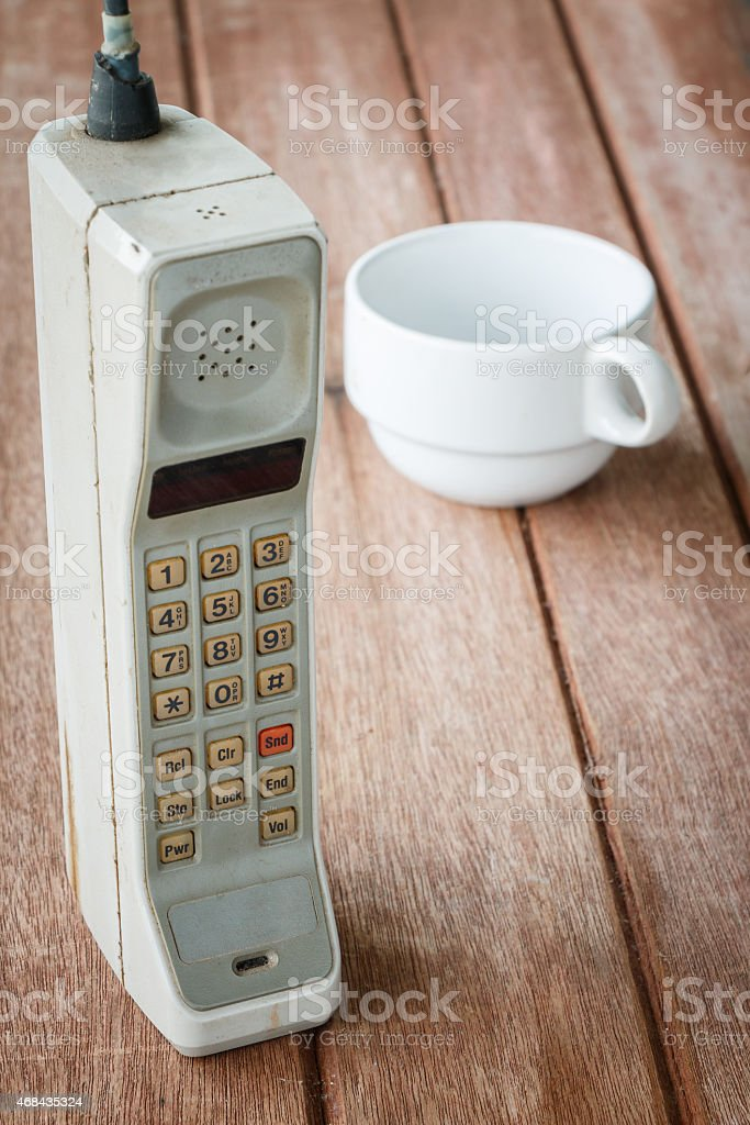 vintage mobile phone with cup stock photo