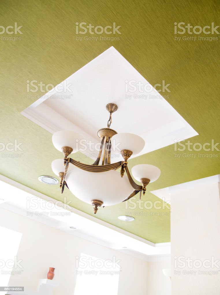 Vintage modern chandelier on green wall stock photo