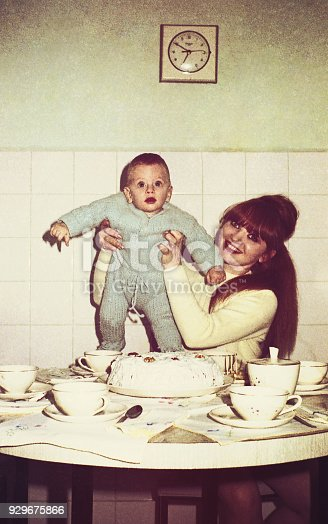 vintage colored image of a mother holding her baby boy in the kitchen.
