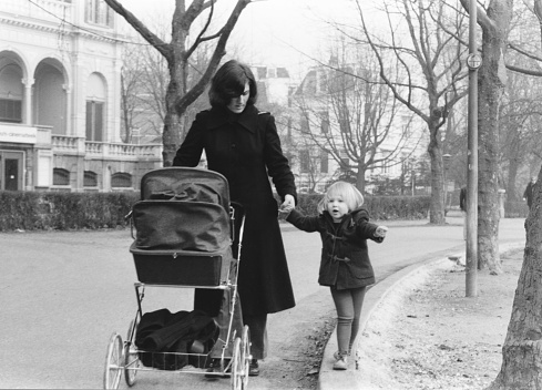 1976 vintage monochrome image of a mother with a long black coat walking hand in hand with her daughter and pushing a classic pram in Vondelpark, Amsterdam, The Netherlands.