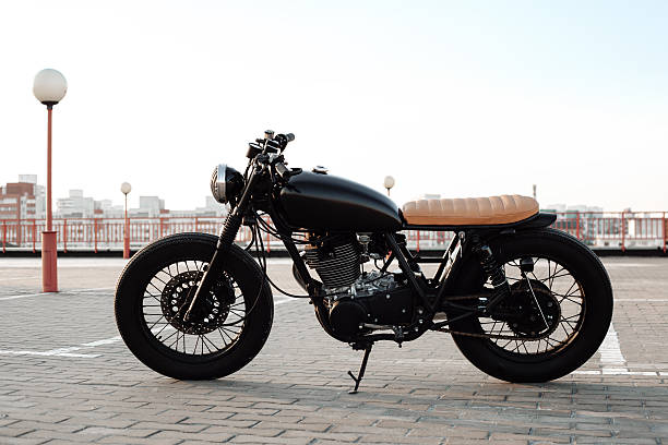 Vintage motorcycle in parking lot during sunset stock photo
