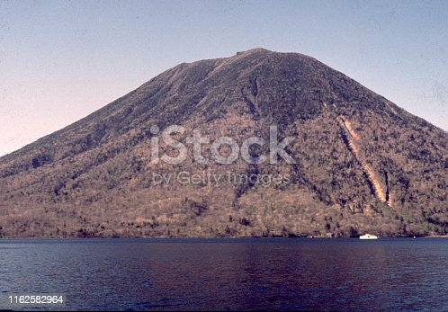 Vintage, authentic archival photograph of mountain in a lake, 1976