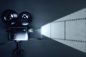 Vintage movie camera with reel of film on grey wall