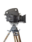 Side view of an old movie film camera on a wooden tripod, isolated on white background.