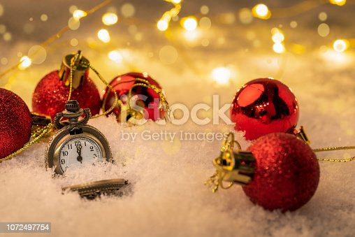 1025550352 istock photo Vintage New year clock and cones covered with snow. 1072497754