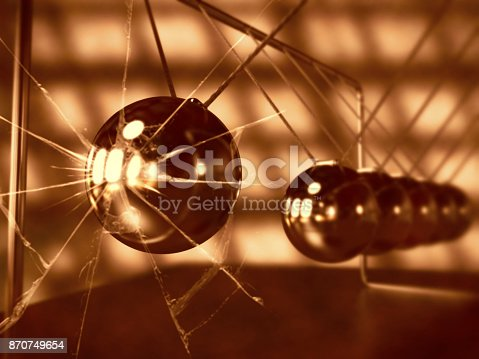 921145928 istock photo vintage Newton's cradle with broken glass, silver cradle on dark surface 870749654
