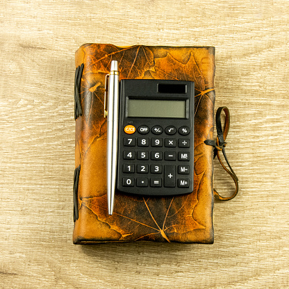 istock Vintage notebook, pen, calculator on a wooden background Top view, flat lay 1213673557