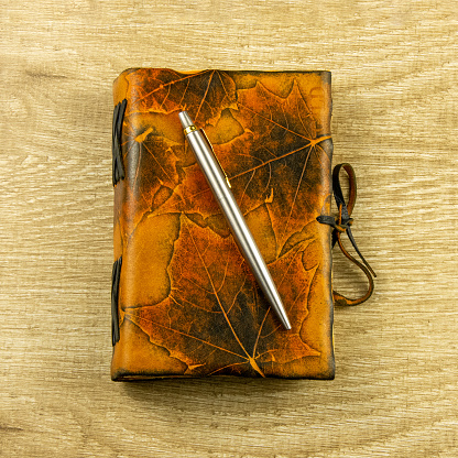 istock Vintage notebook, pen on a wooden background Top view, flat lay 1213673570